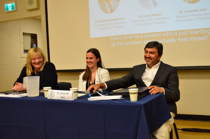 Photo of the three panel speakers, laughing and sitting at desk.